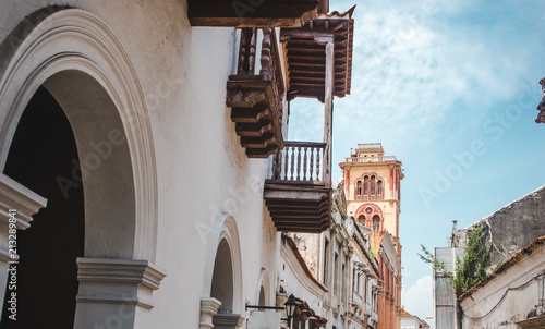 Yellow and orange church bell tower seen at the end of a row of beautiful balconies within the old walls of the historical city of Cartagena, Colombia - 213289841