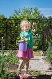 Baby girl in garden with carrot - 213290850