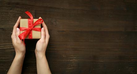 Weihnachten/ Hände halten Geschenk auf Holz