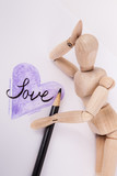 Vertical composition wooden jointed manikin doll laying on a solid white background sketched purple heart love drawn in black ink - 213294076
