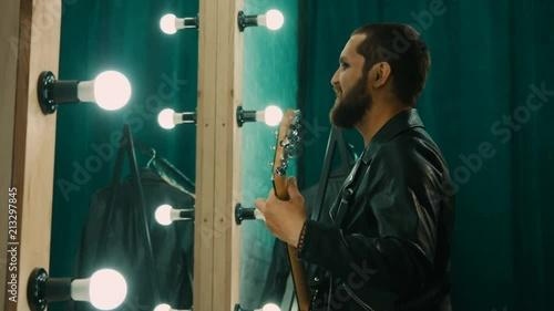 Side view of brutal man in leather jacket and with makeup playing guitar and preparing performance in front of mirror
