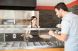 Customer man choosing toppings from counter with women chef taking order - 213299047