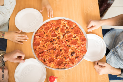 Wall mural Pepperoni cheese pizza on wooden table