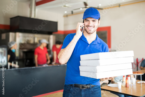 Young pizza man taking an order over the phone in pizza shop