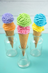 Rainbow Ice Cream Scoops in Waffle Cones on a Teal Table