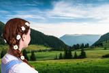 junge Frau im Dirndl schaut auf Alpenlandschaft