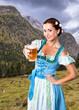 Leinwandbild Motiv junge Frau im Dirndl mit Bier vor Alpenlangschaft
