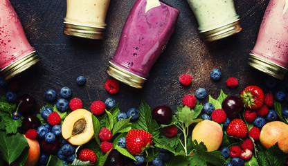 Healthy and useful colorful berry smoothies with yogurt, fresh fruit and raw berries on brown background, top view