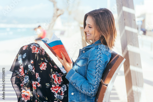 Foto Murales Happy woman relaxing at the seaside with a book