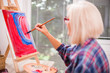 Elderly woman is painting in her home. Retirement hobby.  - 213339845