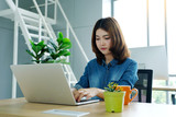 Young asian woman working with laptop computer at office with happy emotion, working at home, office casual lifestyle concept