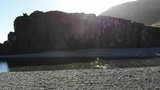 Aerial tracking river boulder with sunbeam shining past in Iceland. - 213382484
