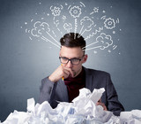 Young businessman sitting behind crumpled paper with drawings of gears and steam over his head - 213390647