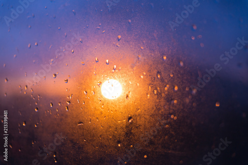 Blurred texture. Sunset after the rain through the glass with droplets.