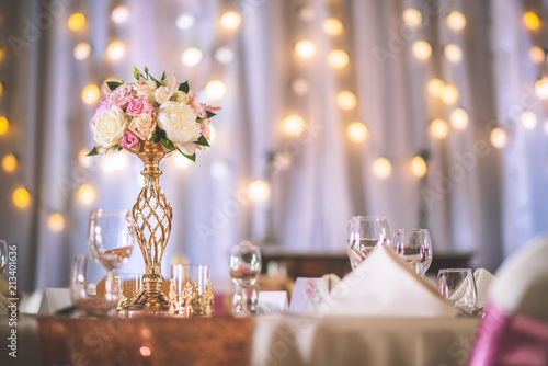 wedding table with exclusive floral arrangement prepared for reception, wedding or event centerpiece in rose gold colour © martingaal