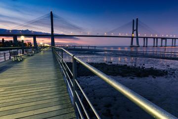 View of amazing Vasco da Gama Bridge at sunset. The Vasco da Gama Bridge crosses the Tagus River, and is one of the longest bridges in the world. Lisbon. Portugal. © vovik_mar