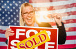Young Woman Holding House Keys and Sold Sign In Front of American Flag