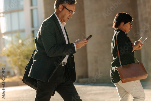 Foto Murales Business people busy using mobile phone while walking on street