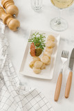 Boiled new potatoes served with sauce and fresh arugula on white plate - 213420472
