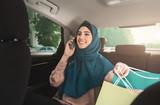 Happy muslim woman talking on smartphone in car - 213447811