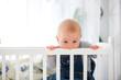 Leinwanddruck Bild - Little toddler boy, crying in crib after waking up