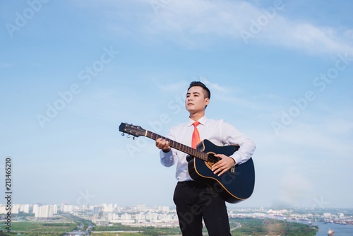 Foto Murales Musical Concept. Casual man playing practicing guitar.