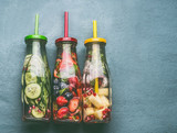 Variety of colorful infused water in bottles with fruits berries, cucumber, herbs and drink straws on gray background, top view. Tasty summer clean beverages for  healthy lifestyle and fitness - 213466277
