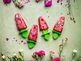 Pink homemade fruits and berries ice cream or popsicles on teal rustic green table background, decorated with garden flowers, top view.  Country style summer food concept - 213468021