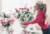 Florist women in red shirt, make beautiful big festive event classical bouquet with roses and other flowers in urn vase on table at window, lifestyle - 213471213