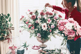 Florist women make beautiful big festive event classical bouquet with roses and other flowers in urn vase on table at window, lifestyle - 213471257