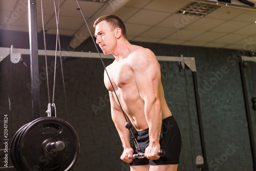 Wall mural Strong muscular bodybuilder doing exercise in the gym. Fitness training