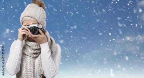 Fototapeta Frau macht Fotos vor winterlichem Hintergrund