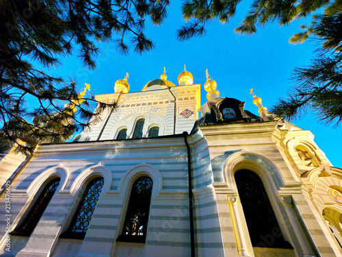 Golden domes of the church with crosses against the background of clear blue sky and pine branches - 213476695