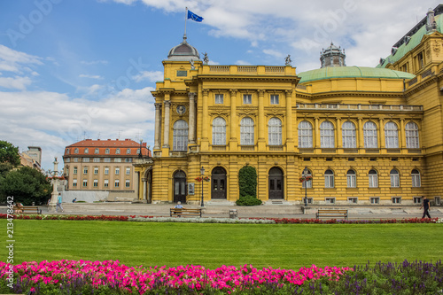 opera house building architecture yellow facade with colorful flower bed on foreground - 213478642