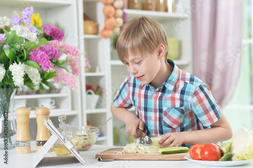 Cute little boy making dinner - 213479652