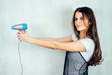 Indian woman holding blue hair dryer in hands on white background © Юрий Красильников