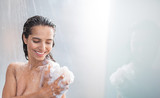 Portrait of beaming woman rubbing body with foam while standing under steam of water. Copy space - 213497642