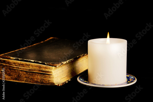 Magic book with candle over black background like esoteric and