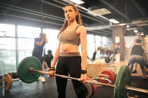 Strong woman lifting up weights in the gym