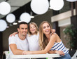 Waist up portrait of joyful couple sitting with child in bar at table. Small girl is pointing with finger while smiling woman and man are looking sideways. They are having fun while waiting for order