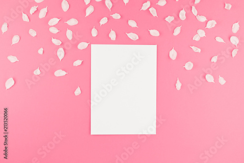 Foto Murales Flat lay of white postcard mock up with petals
