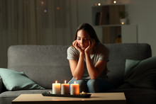 """Постер, картина, фотообои """"Distracted woman looking at candles light during blackout"""""""