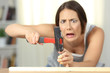 Leinwanddruck Bild - Woman hitting finger with a hammer