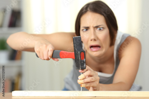 Woman hitting finger with a hammer