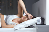 Woman suffering headache in the bed at home in the night - 213544239