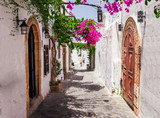 Fototapeta Uliczki - Narrow street in Lindos town on Rhodes island, Dodecanese, Greece. Beautiful scenic old ancient white houses with flowers. Famous tourist destination in South Europe © oleg_p_100