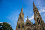 gothic church facade from below on blue blurred sky background in summer colorful bright day time - 213553692
