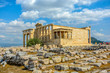 View of the Erechtheion temple at the Athens Acropolis in Athens Greece on a warm summer day with Lykavittos Hill in the background