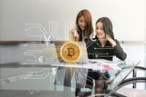 Two Asian young Businesswoman sitting and using the technology laptop with Bitcoins mockup over the photo of FINTECH connection hologram in workplace,blockchain and bitcoin concept