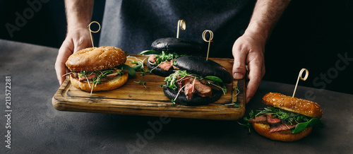 Man holds board different burgers with grilled beef meat - 213572281